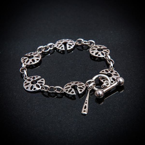 Fen Bracelet by Patricia Dudgeon Designs Delicate bracelet made up of cut out roundels, complete with T bar and ring with long dropper fastener. Hallmarked Sterling silver