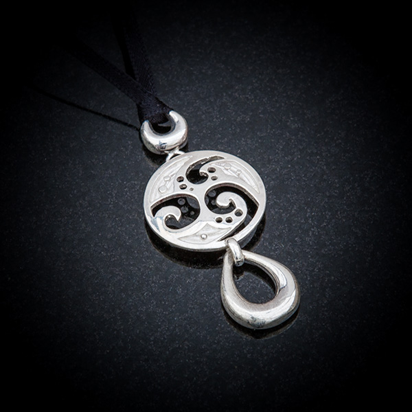 Sterling silver pendant with Celtic disc and teardrop dropper on black silk ribbon. Hallmarked Sterling silver.