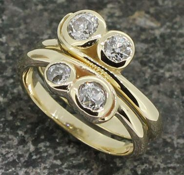 Two 18ct yellow gold two diamond wrap around shanked rings